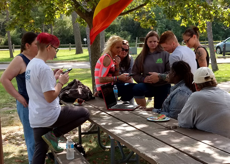 Image of transgender group gathered around a picnic table